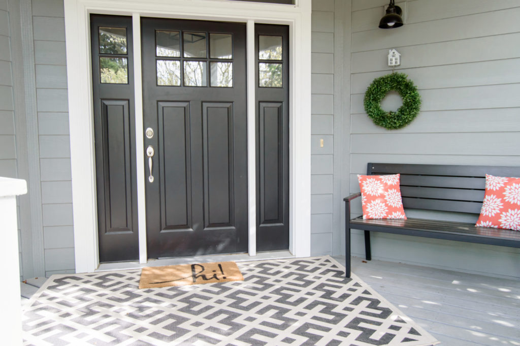 Front porch after remodel, new paint, new black door, wreath, welcome mat, bench.