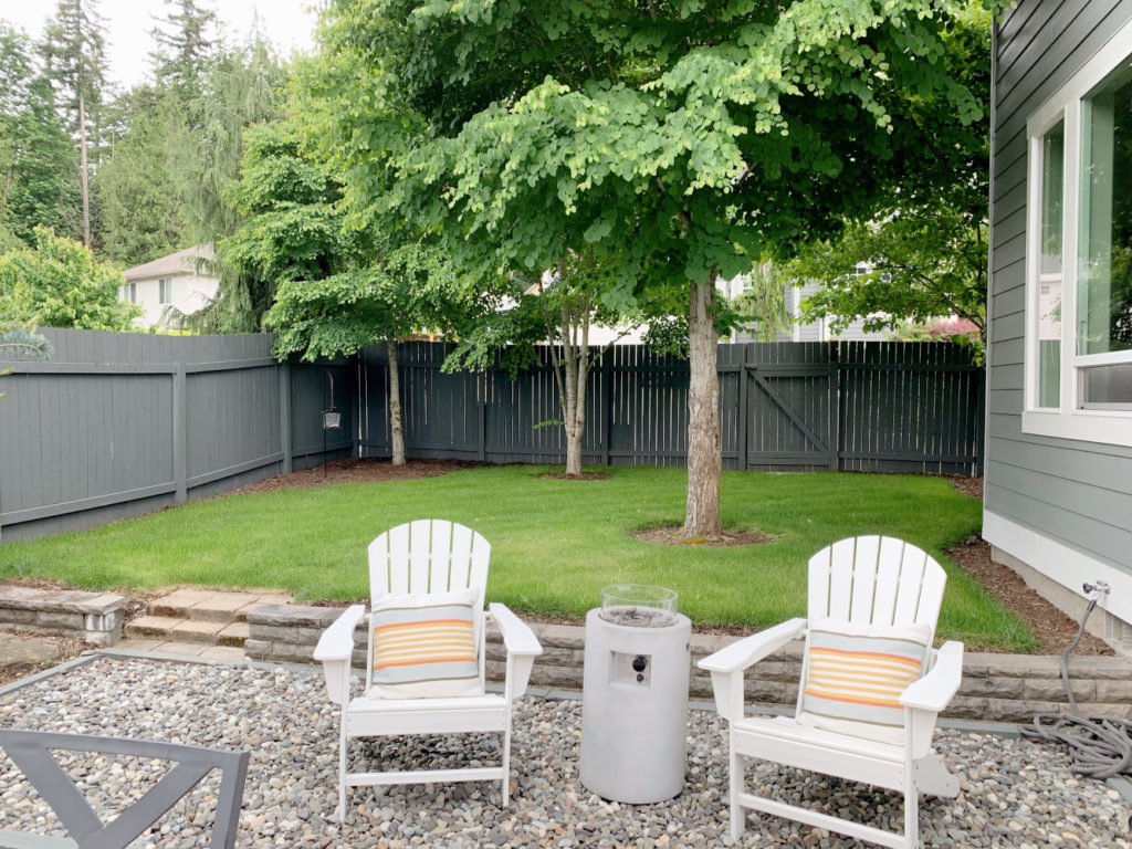Backyard with fence painted gray, house painted gray.